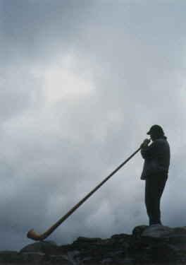 Photo: Playing Alphorn in the Mountain Mist